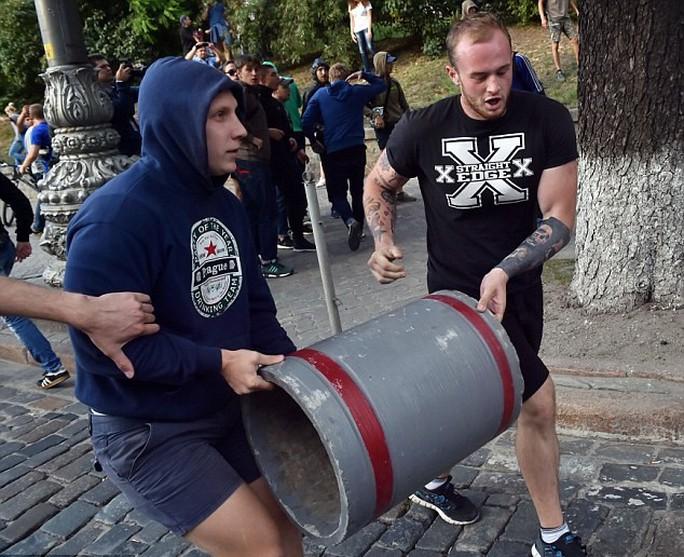 Hai CĐV Legia khiêng vũ khí chiến đấu với cảnh sát