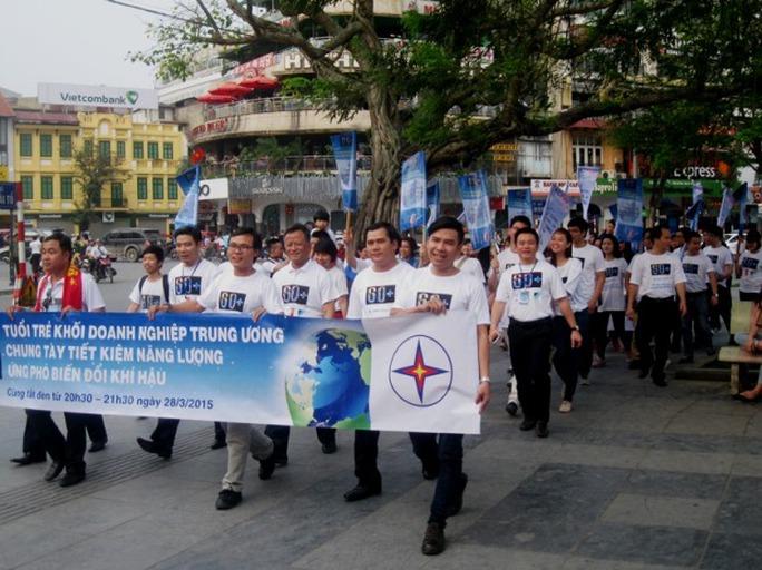 """Đoàn người diễu hành quanh Hồ Gươm với băng rôn mang thông điệp kêu gọi """"Chung tay tiết kiệm năng lượng, ứng phó biến đổi khí hậu"""""""