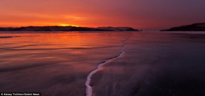 Nhiếp ảnh gia Alexey Trofimov thức dậy lúc bình minh để bắt được khoảnh khắc vết nứt dưới bầu trời màu cam rực rỡ