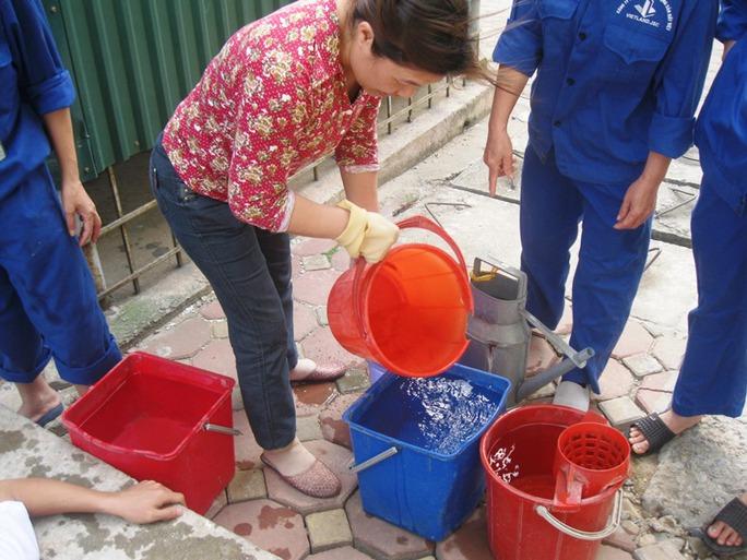 Người dân đang múc nước tại bể chứa