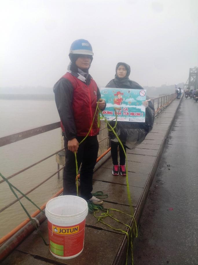 Mặc cho thời tiết giá rét mưa phùn, các bạn sinh viên tình nguyện vẫn đứng ở cầu Long Biên hướng dẫn, giúp đỡ người dân thả cá chép mà không thả túi nilon xuống sông và gom rác tại cầu