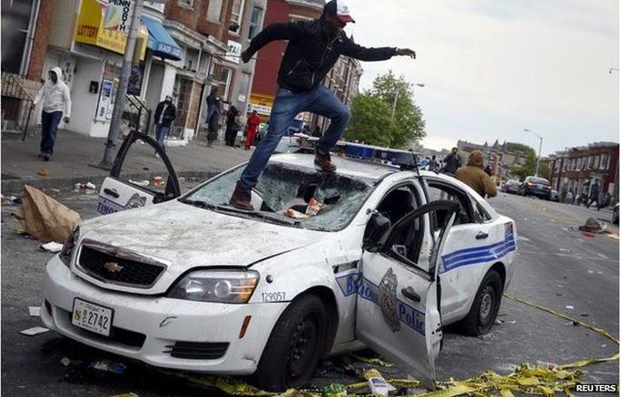 Xe cảnh sát bị đập phá. Ảnh: AP