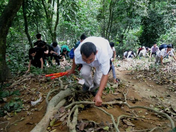 Nhiều người tay nắm rễ cây, tay nắm thẻ hương leo núi, bất chấp những con dốc sâu thăm thẳm rất nguy hiểm