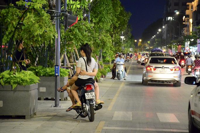 Một cặp đôi hẹn hò ngay dưới lòng đường trên phố đi bộ Nguyễn Huệ, bất chấp dòng xe cộ qua lại đông đúc.  - Ảnh: Thăng Bình