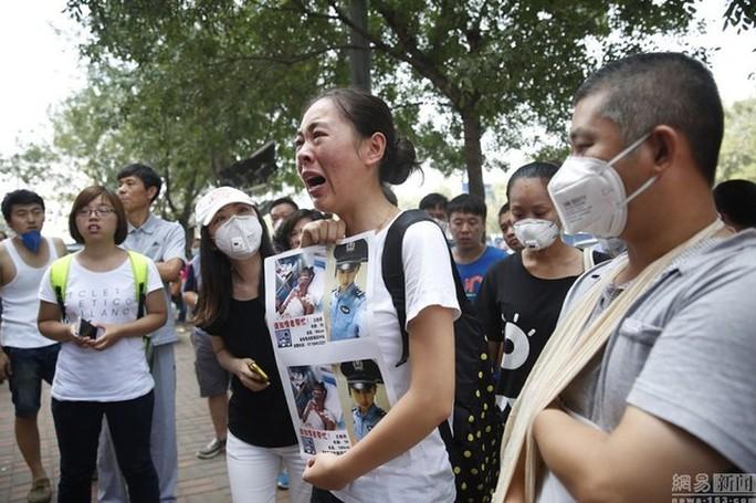 Một phụ nữ tìm thông tin người thân. Ảnh: Shanghaiist