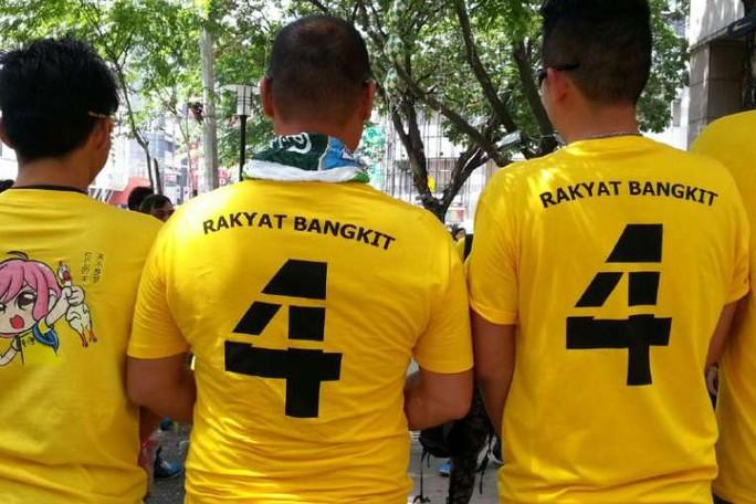 """người biểu tình mặc áo thun màu vàng in chữ """"Rakyat Bangkit 4"""". Ảnh: Straits Times"""
