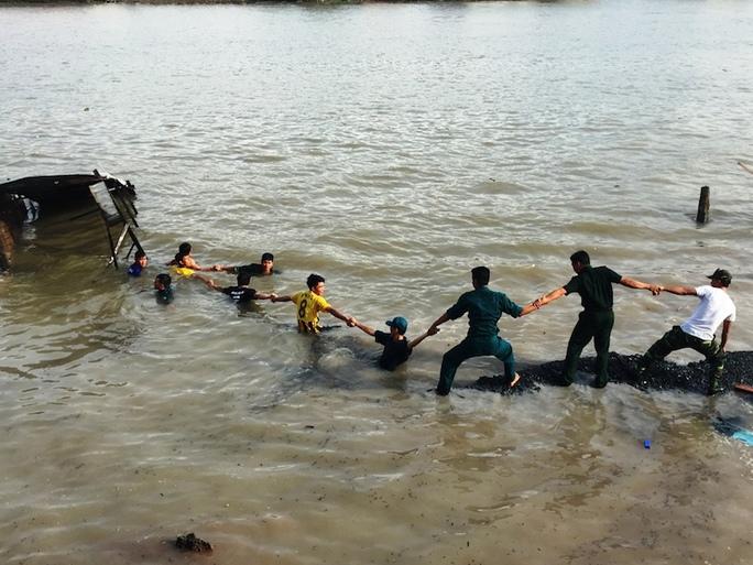 Người dna6 cùng bộ đội giúp vân trục vớt tài sản rơi xuống sông.