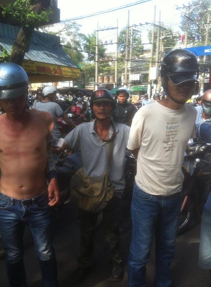"""Hai tên trộm quần áo Hiếu và Quốc bị """"hiệp sĩ"""" Trần Văn Hoàng (giữa) cùng đồng đội bắt giữ."""