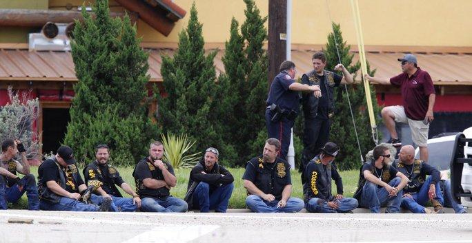 Thành viên 3 CLB mô-tô ngồi chờ bên ngoài trong khi cảnh sát điều tra hiện trường. Ảnh: AP
