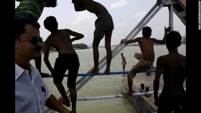 Nhiều người dân Ấn Độ tắm sông để dập tắt cái nóng như thiêu như đốt. Ảnh: EPA