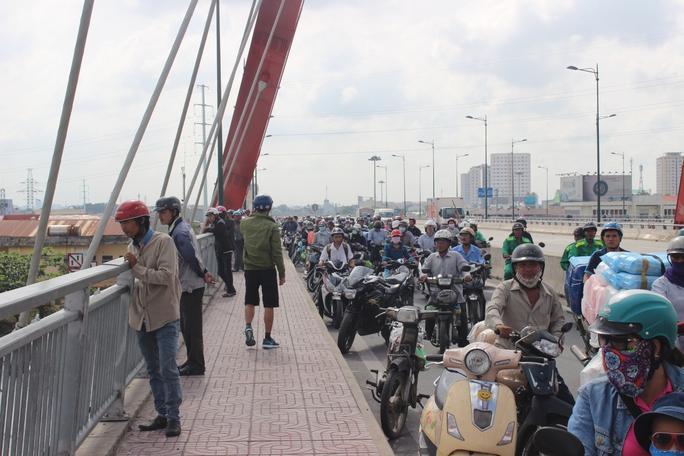 Tại cầu Bình Lợi mới, hàng trăm người dân hiếu kỳ đứng theo dõi khiến giao thông bị ùn ứ cục bộ