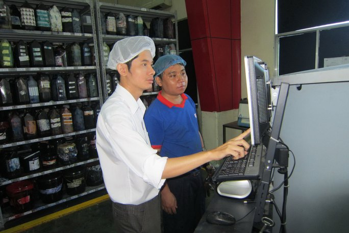 Anh Lê Quốc Dũng (trái), phụ trách quản lý hệ thống chất lượng và môi trường Công ty CP In Nhãn hàng An Lạc, hướng dẫn công nhân thao tác trên máy tính