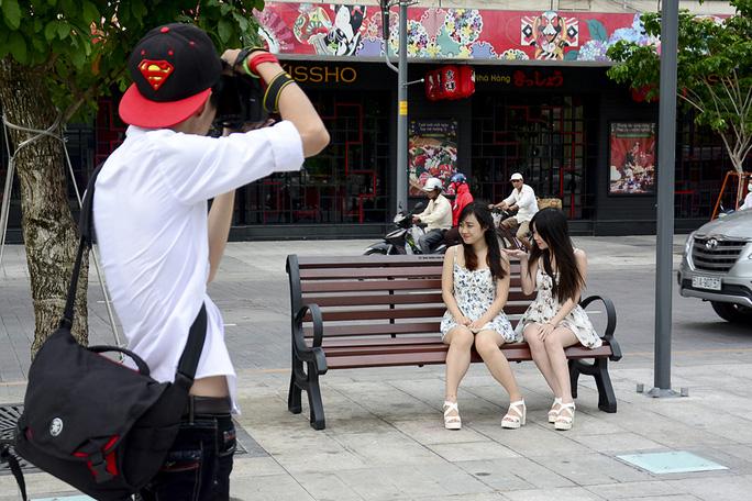 Các bạn trẻ tạo dáng bên ghế gỗ để chụp ảnh. Ảnh: Thăng Bình