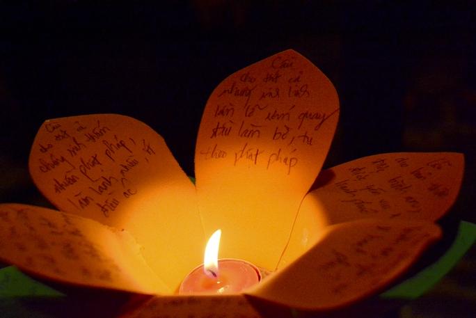 Họ ghi những điều ước lên hoa đăng. Ảnh: Thăng Bình.