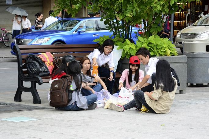 Do số lượng quá đông nên nhóm bạn trẻ dùng ghế gỗ để đồ đạc rồi ngồi bệt xuống đất để vui chơi. ảnh: Thăng Bình