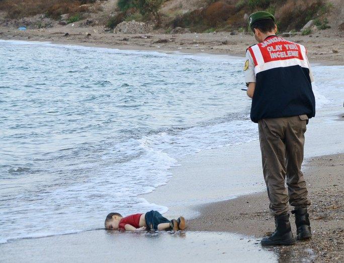 Cậu bé Aylan nằm bất động trên bãi biển. Ảnh: Independent