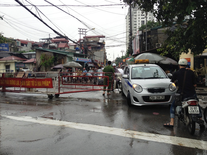 Đến 16 giờ 30, lực lượng Công an phường Định Công phải đóng barie không cho xe lưu thông vào khu phố bị ngập