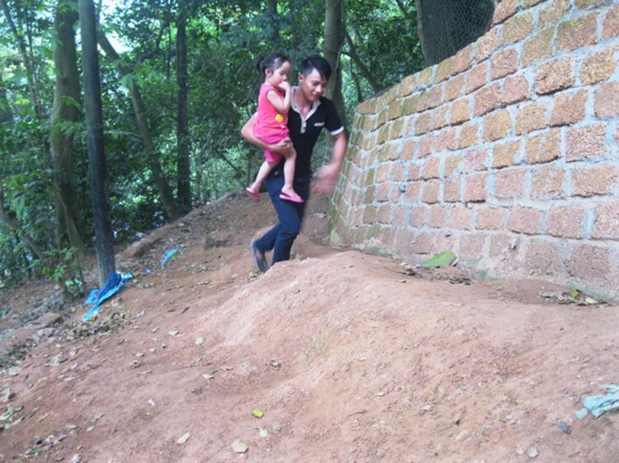 Bế cả con nhỏ leo trèo dốc
