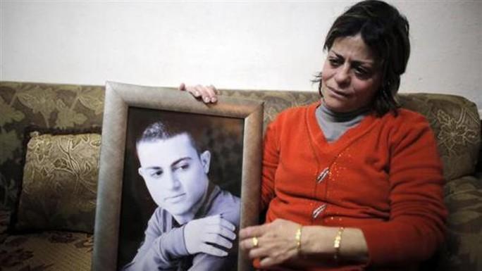 Mẹ Muhammad Musallam cầm ảnh con trai. Ảnh: Press Tv