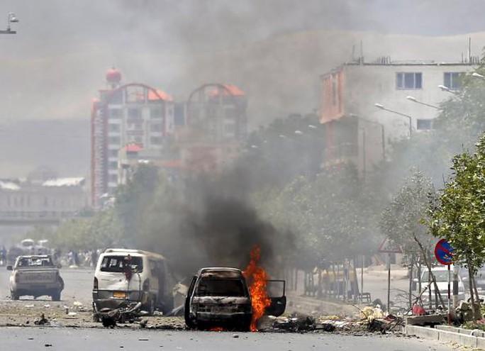 Một chiếc xe bốc cháy gần trụ sở quốc ội Afghanistan ở Kabul hôm 22-6. Ảnh: Reuters