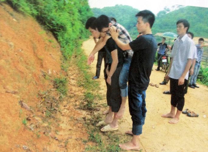 Thực nghiệm hiện trường: Tiếp cõng nạn nhân lên đồi với sự hỗ trợ của đối tượng khác - ảnh Hồ sơ vụ án