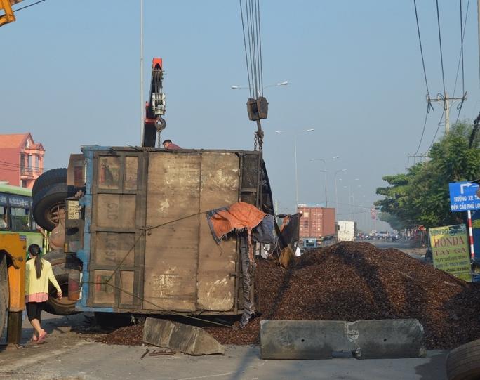 Hàng tấn vỏ hạt điều đổ tràn mặt đường sau khi chiếc xe tải lật nghiêng