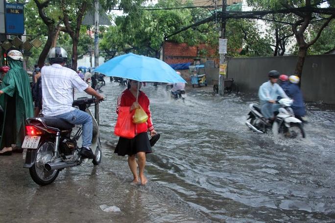 Dù đi đường bị ngập nước nhưng người dân tỏ vẻ vui mừng vì cơn mữa đã giúp thời tiết được mát mẻ.