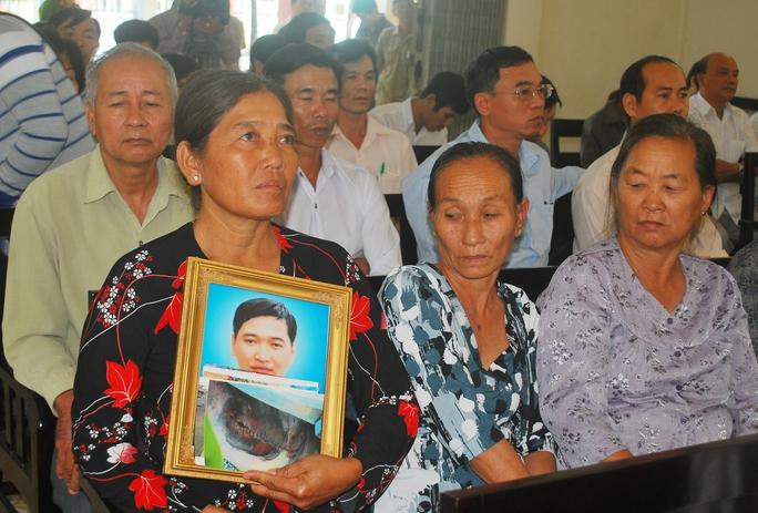 Bà Đặng Thị Nhu (mẹ ruột nạn nhân) mang theo di ảnh con trai duy nhất trong gia đình đến nghe TAND tỉnh Đồng Tháp xét xử.