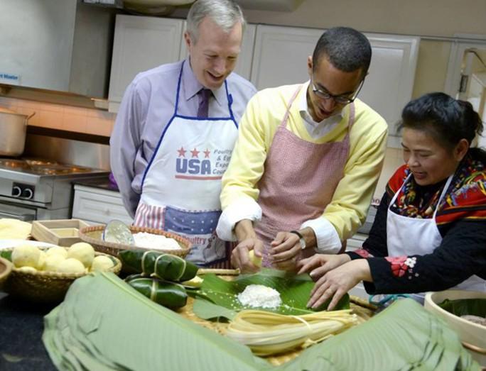 Bạn đời của Đại sứ, ông Clayton Bond (giữa), cũng rất hào hứng học gói bánh chưng