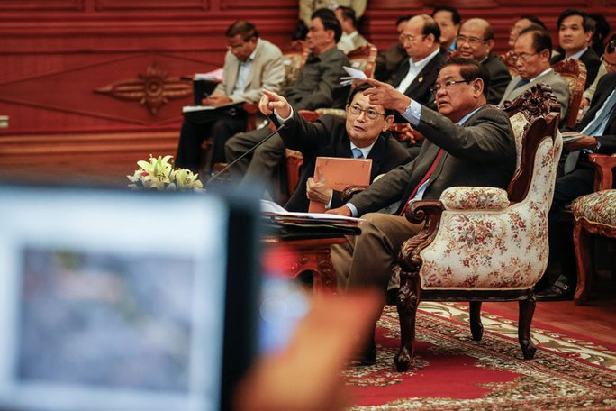 Interior Minister Sar Kheng, right, and border affairs chief Var Kimhong gesture during a meeting in Phnom Penh on Tuesday with government officials from the provinces bordering Vietnam. (Siv Channa/The Cambodia Daily)