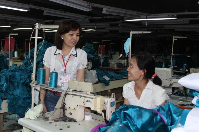 Bà Nguyễn Thị Nguyệt, Chủ tịch Công đoàn Công ty May Cường Tài, thăm hỏi  công nhân Ảnh: THANH NGA