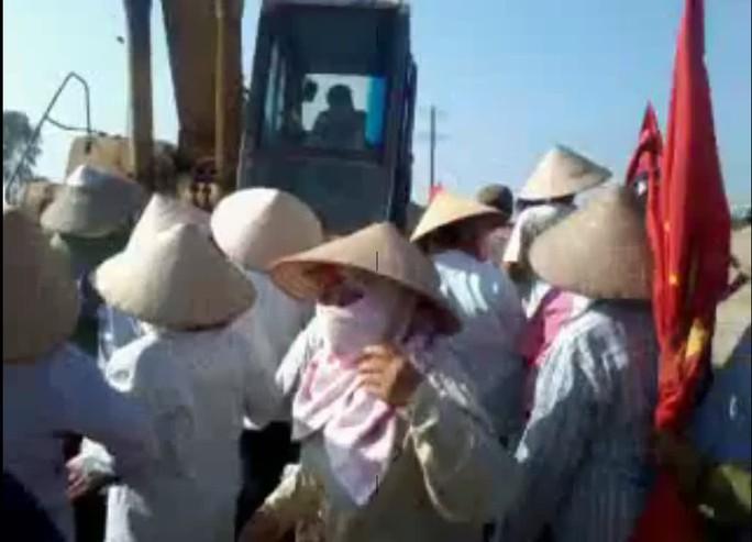 Hình ảnh trong clip cảnh người dân vây quanh chiếc xe máy xúc bánh xích - Ảnh cắt từ clip trên mạng