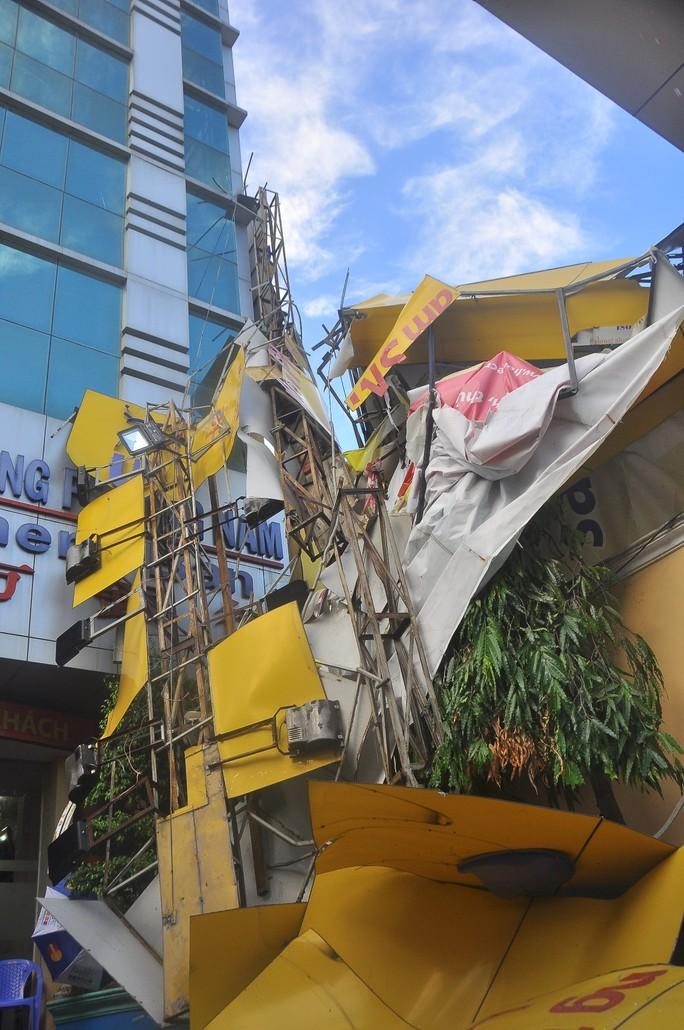 Mưa lớn kèm gió lốc làm biển hiệu của một cửa hàng điền tử trên đường Lê Văn Việt bị gãy đổ