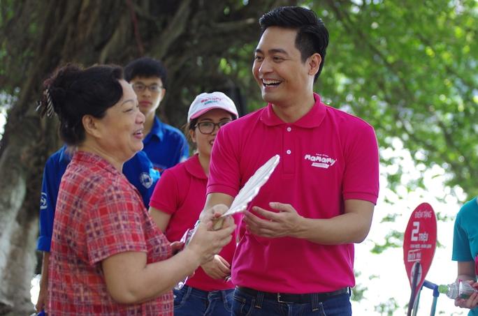 MC Phan Anh tươi cười trò chuyện với một người đi đường