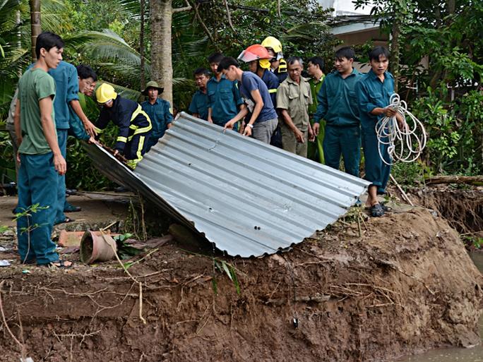 Lực lượng chức năng vớt tài sản của nhà bà Trang bị sụp xuống sông.
