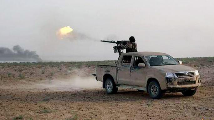 Một tay súng IS bắn về phía quân đội chính phủ. Ảnh: Islamic State militants