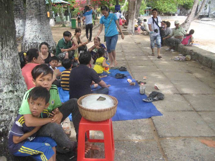 Du khách thuê bạt ngồi la liệt trên lối đi đến bến tàu tham quan Hòn Phụ Tử