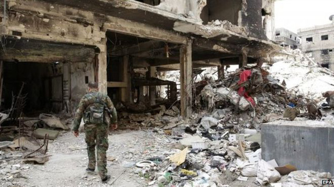 A Palestinian fighter walks through the rubble of the Yarmouk camp