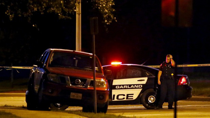 A police officer stands near the suspects vehicle after a shooting outside the Muhammad Art Exhibit and Contest on Sunday.