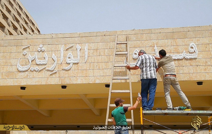 Refurbishment: Workmen use sledgehammers to remove carvings on the side of the building and replace them with simplistic Arabic writing