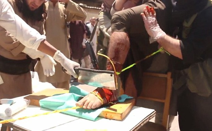 Cruel: The first mans foot is covered in what appears to be red antiseptic solution before an ISIS militant chops off his foot with a meat cleaver