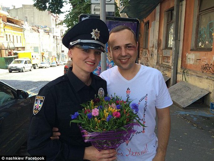 From Ukraine, with love: 2,000 new police officers have taken to the streets of Kiev today in an attempt to reform the countrys police force (pictured, a female officer hands flowers to an injured man)