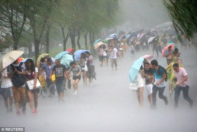 People hold umbrellas in heavy rain as Typhoon Soudelor approaches, in Hangzhou, Zhejiang province