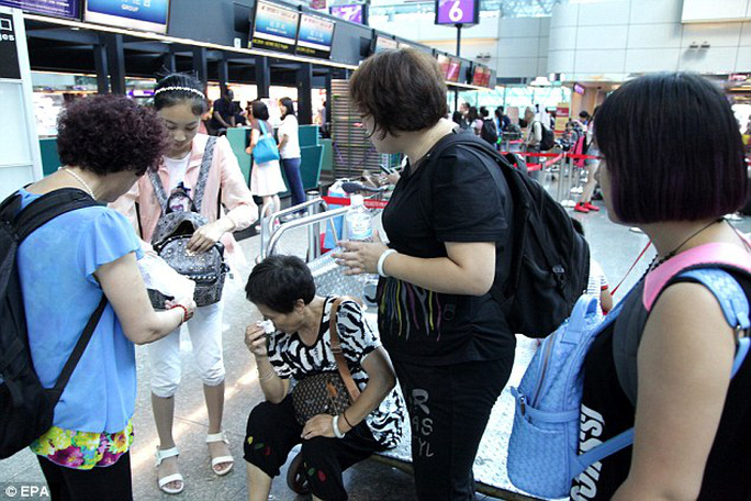 A Chinese tourist at Taiwan Airport is distraught by the news that the return flight to China was cancelled