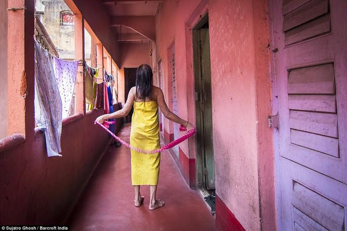 Bà Maya Banarjee, 72 tuổi, đang hong khô tóc trong một nhà chứa. Ảnh: DAILY MAIL