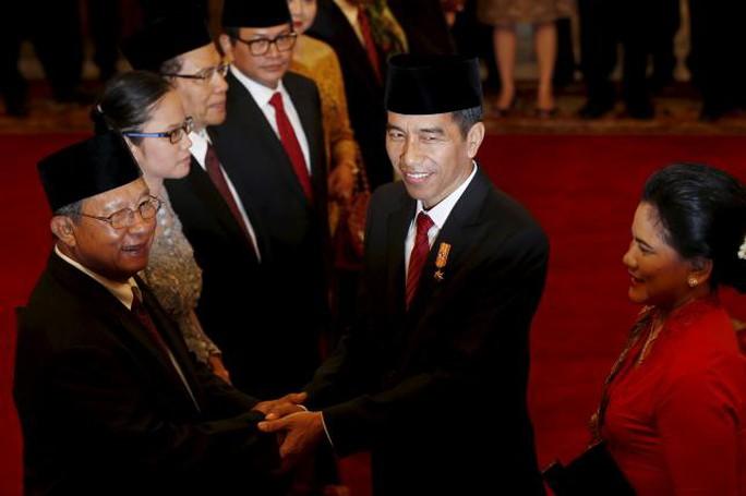 Tổng thống Joko Widodo (giữa) chúc mừng tân Bộ trưởng Kinh tế Darmin Nasution (trái) sau lễ nhậm chức hôm 12-8 Ảnh: Reuters
