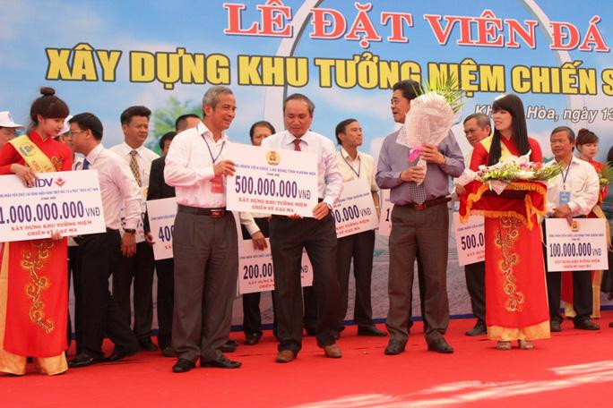 Ông Đặng Ngọc Tùng (bìa trái), tiếp nhận ủng hộ kinh phí xây dựng Khu tưởng niệm chiến sĩ Gạc Ma từ đại diện LĐLĐ tỉnh Khánh Hòa    ẢNH: KỲ NAM