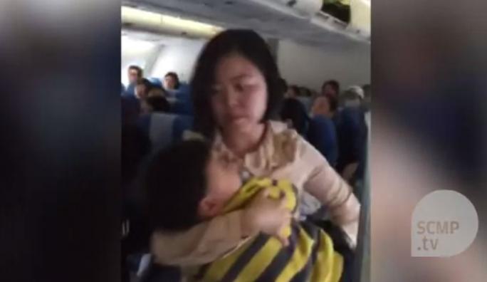 Người phụ nữ bế con trai 3 tuổi khỏi máy bay. Ảnh: SCMP