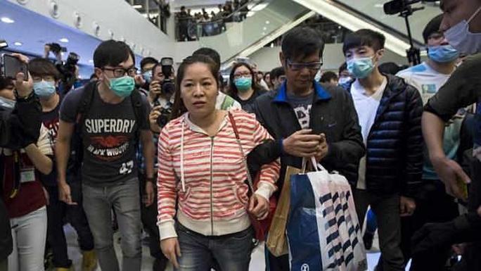 Người phụ nữ Trung Quốc (giữa) bị những người biểu tình Hồng Kông vây quanh. Ảnh: Reuters