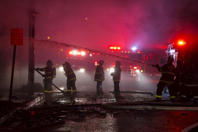 Lính cứu hỏa vất vả dập lửa rạng sáng 28-4. Ảnh: Reuters